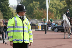 British police officer. Tuesday, October 2, 2007: A british police officer is watching the changing of the guard at Buckingham Palace, in London, UK Royalty Free Stock Image