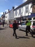 British police rush to an incident in street. ST ALBANS, UK - APRIL 19, 2016 British police rush to an incident on an English high street Royalty Free Stock Image