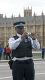 British policeman with photo camera Royalty Free Stock Photos