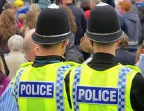 British policemen. Two British policemen watching during crowded street event Stock Photo