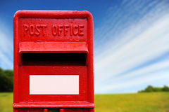 British Post Box. Bright red traditional British post box with a country background stock photo