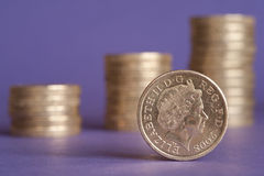British pound. Macro of one pound coin with out of focus rising coin stacks in the background Royalty Free Stock Photography