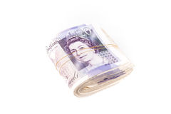 British pound sterling bank notes. Elastic bands secure a bulky roll of British pound sterling bank notes with the Queen's face from a 20 showing on top Stock Images