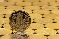 British pound coin on a background of more money. British money, pound coin showing heraldic lion, unicorn, shield and crown on a background of pound coins Stock Photo