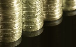 British pound coins. Gradually decreasing stacks of one pound english coins on black background with reflection underneath Royalty Free Stock Photo