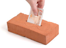 British Pound deposit into building brick. British Pound-bank note in a piggy bank or tissue box like brick Stock Image
