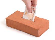 British Pound deposit into building brick. British Pound-bank note in a piggy bank or tissue box like brick Stock Image