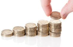 British pound sterling coins stack. In columns symbolizing wealth growth with fingers put a pound coin over it Royalty Free Stock Photography