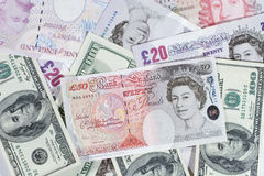 British pounds and dollars. Bunch of twenty-pound notes, fifty-pound notes and one-hundred dollar bills Royalty Free Stock Photos