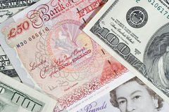 British pounds and dollars. Bunch of twenty-pound notes, fifty-pound notes and one-hundred dollar bills Stock Photo