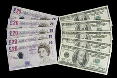 British pounds and dollars. Five twenty-pound notes and five one-hundred dollar bills (isolated on black Stock Photos