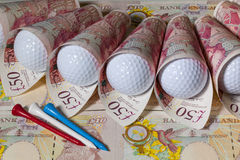 British pounds and golf balls Stock Images