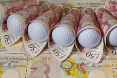 British pounds and golf balls Royalty Free Stock Photography