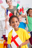 British preschooler. A happy little british preschooler holding flag with classmates waving flags in background Stock Images