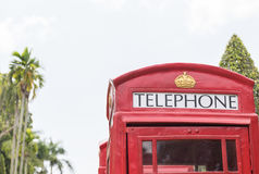 British red telephone booth. Close up classic British red telephone booth in garden Royalty Free Stock Photo