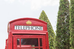 British red telephone booth. Close up classic British red telephone booth in garden Royalty Free Stock Images