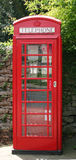 British Red Telephone Box. A British Red Telephone box against a stone wall Royalty Free Stock Photo