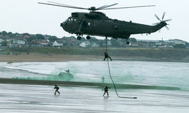 British Royal Marine Commando Helicopter. British Royal Marine Commandos fast-line from a helicopter perform a beach assault demonstration for the public at the Stock Images