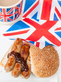 British sausage sandwich with, brown sauce, cup of tea and flag. Detail of British sausage sandwich on a sesame bun with brown sauce cup of tea in a union jack Stock Image