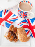 British sausage sandwich with, brown sauce, cup of tea and flag Royalty Free Stock Photo