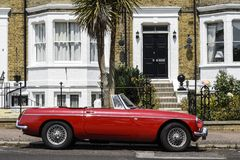 British scene. English scene. MG B classic car parked outside townhouse stock photo