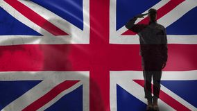 British soldier silhouette saluting against national flag, independence day. Stock footage stock footage