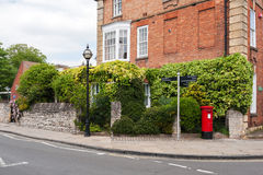 British street scene. Traditional red mail box, old lamp and bricked building at the street corner. Typical british street scene Royalty Free Stock Photo