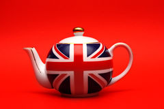 British teapot. Teapot with English flag close up on red background Royalty Free Stock Photography