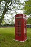 British Telephone Booth. Red British telephone booth under tree in field of green grass Royalty Free Stock Image