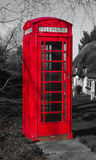 British Telephone Box. Near a thatched cottage in England Royalty Free Stock Photo