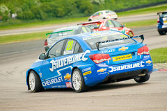 British Touring cars. THRUXTON, UNITED KINGDOM - MAY 1, 2011: Alex MacDowell lifts a wheel while cornering his Silverline Chevrolet Cruze at the British Touring Stock Photos