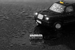 British traditional black cab taxi toy car with the word cab on beads. In the wet royalty free stock photos