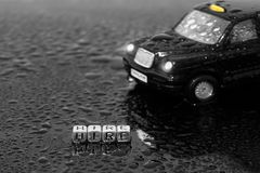 British traditional black cab taxi toy car with the word hire on beads. In the wet stock image