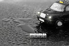 British traditional black cab taxi toy car with the word taxi on beads. In the wet stock images