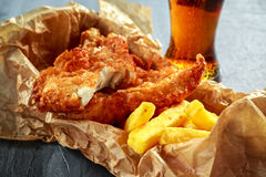 British Traditional Fish and chips in crumpled paper with cold beer. Stock Image