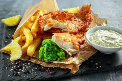 British Traditional Fish and chips with mashed peas, tartar sauce on crumpled paper. stock image