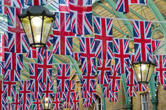 British Union flags in rows with lantern. British Union Jack flags hanging in rows from roof with old decorative lantern Stock Photo