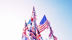 British Union Jack and American flags of the United States waving against blue sky. Saturated colors British Union Jack and American flags of the United States stock footage