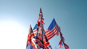 British Union Jack and American flags of the United States waving against blue sky. Vivid colors of British Union Jack and American flags of the United States stock footage