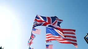UK USA flag waving. British Union Jack and American flags of the United States waving slow motion against blue sky on a warm clear sky sunny day marking the