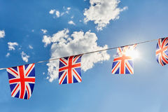 British Union Jack bunting flags against blue sky with sun. Light Royalty Free Stock Photography