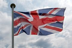 British Union Jack Flag Against Cloudy Sky. British Union Jack flag flying against a cloudy sky stock image