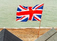 British Union Jack flag flying from a pole on beach huts at the. Edge of the sea on a pebble beach in Kent, England royalty free stock photos