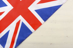 British Union Jack Flag on White Wood Background. British Union Jack Flag on white wood shabby chic table with copy space for your text here Royalty Free Stock Photo