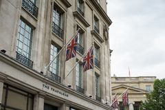 British Union Jack flags on flagpoles in front of a building in West London near Trafalgar Square. royalty free stock image