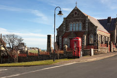 British urbanscape. Old british phone box next to anglosaxon church on a street in the Isle of man, also known simply as Mann, is a self-governing crown Royalty Free Stock Photos