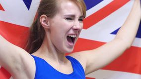 British Young Woman Celebrates holding the British Flag in Slow Motion. High quality royalty free stock images