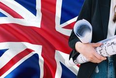 Britse de holdingsblauwdruk van de Architectenvrouw tegen golvende de vlagachtergrond van het Verenigd Koninkrijk Bouw en archite stock fotografie