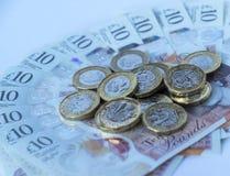 Britse pondmuntstukken die op een semi cirkel van tien pondennota's liggen Stock Afbeelding
