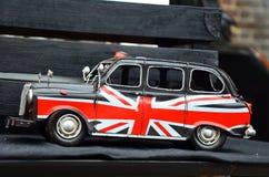 Britse taxi met vlag in Londen Stock Foto